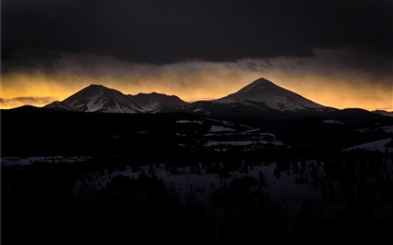 Setting sun behind mountains in Silverthorne Mac wallpaper