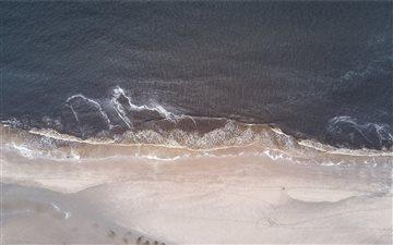 Sea washing ashore drone ... Mac wallpaper