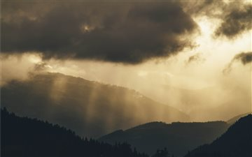 Faint sun rays over hills Mac wallpaper
