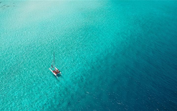 A catamaran sails across ... All Mac wallpaper