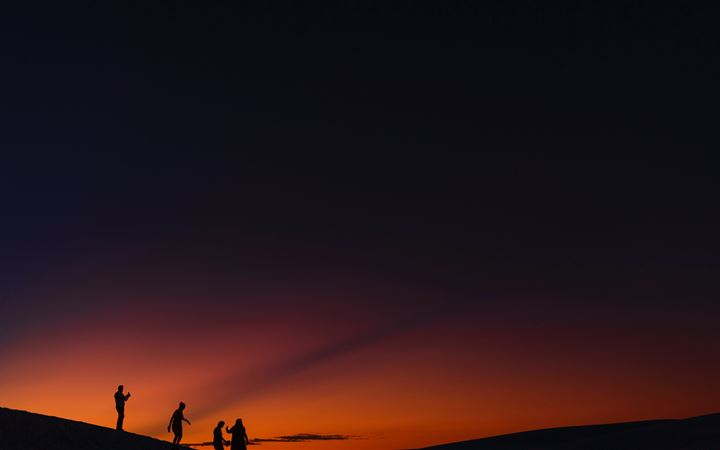 four people standing during golden hour All Mac wallpaper
