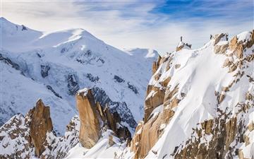 A hiker on a snowy peak Mac wallpaper