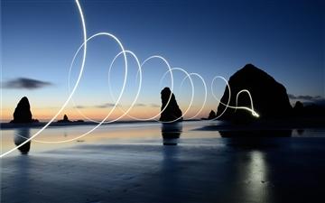 Light painting spirals over the water Mac wallpaper