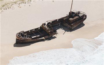 wrecked brown ship on sea... Mac wallpaper