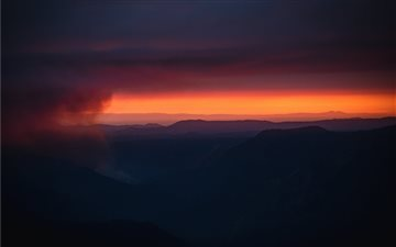 The sun sets behind a smo... Mac wallpaper