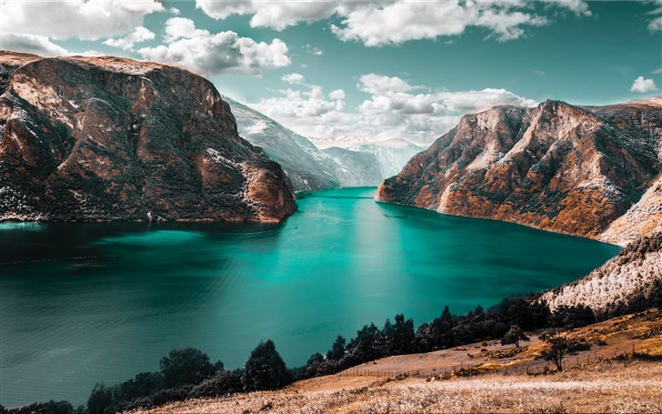 body of water between brown mountains Mac Wallpaper