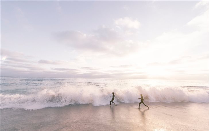 two person running on seaside beach during daytime Mac Wallpaper