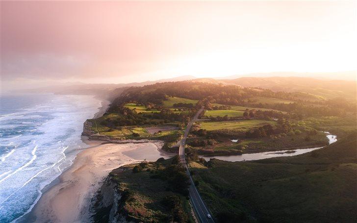 aerial photography of green field beside beach Mac Wallpaper