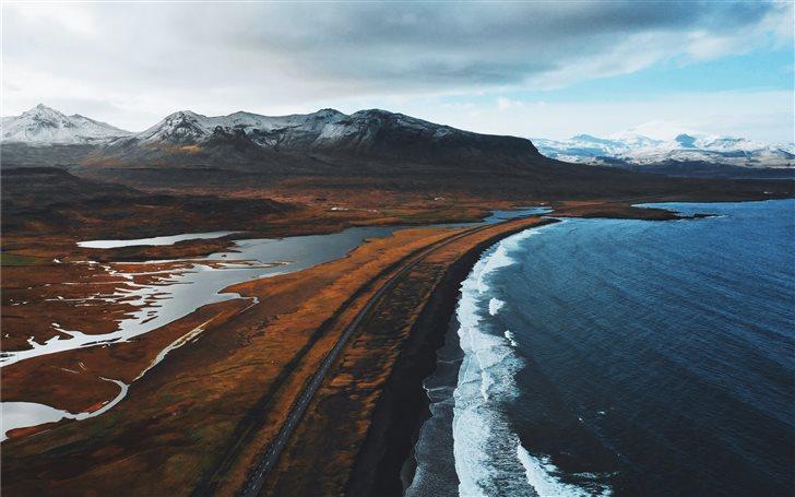 brown mountain near ocean Mac Wallpaper