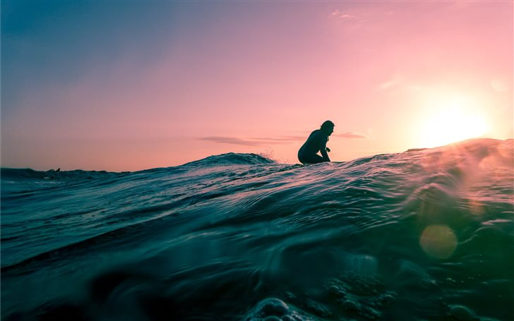 man surfing on ocean water during golden hour Mac Wallpaper