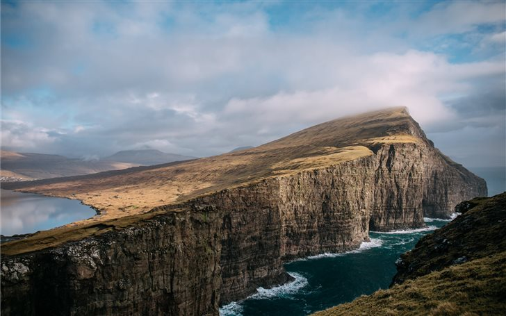 brown cliff near body of water under eblue sky Mac Wallpaper