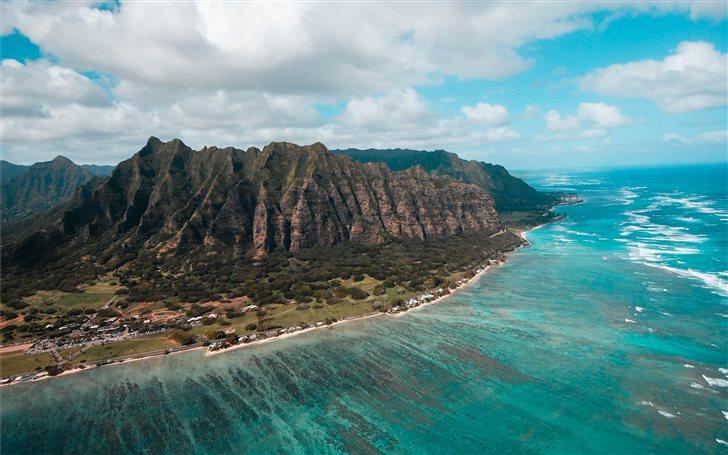 island surround by green sea under cloudy sky Mac Wallpaper