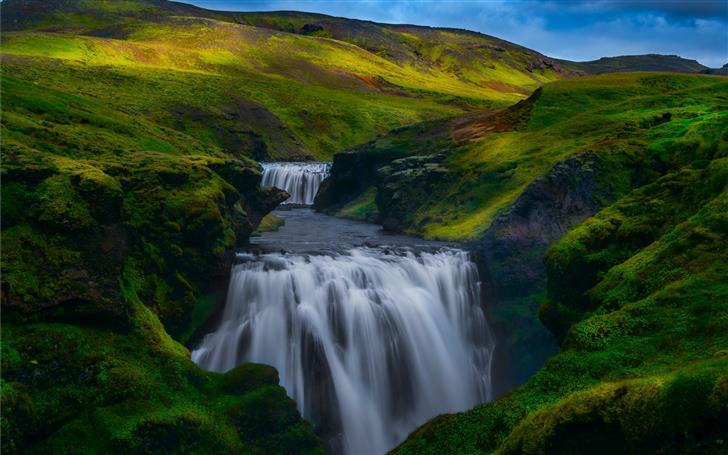 waterfalls between grass covered hills during dayt Mac Wallpaper