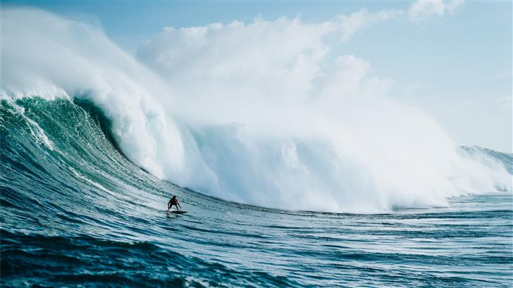 person riding on surfboard with waves behind Mac Wallpaper