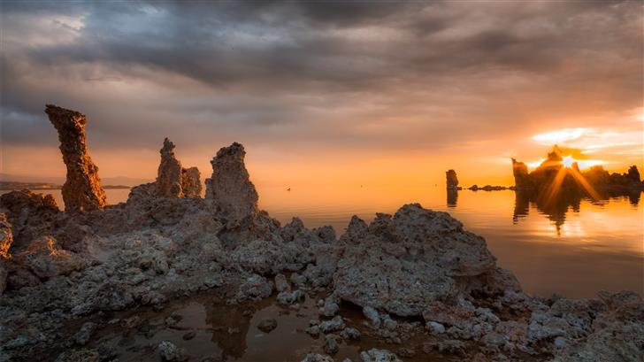 rock formations near calm body of water Mac Wallpaper