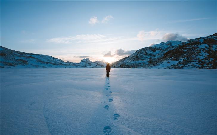 person walking on snow field leaving foot prints Mac Wallpaper