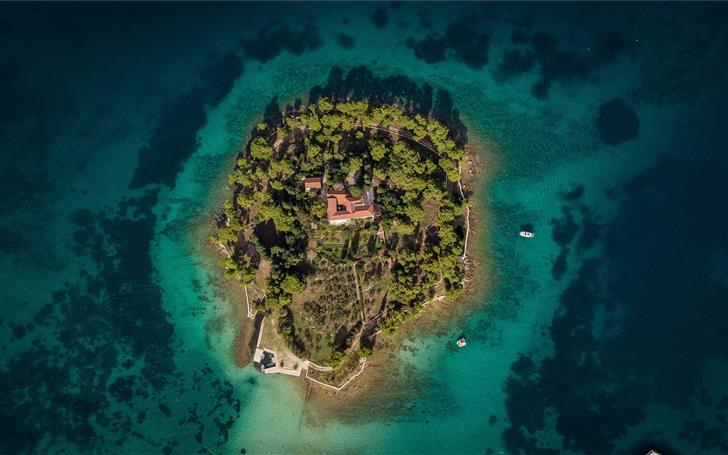 aerial photography of island surrounded by sea dur Mac Wallpaper