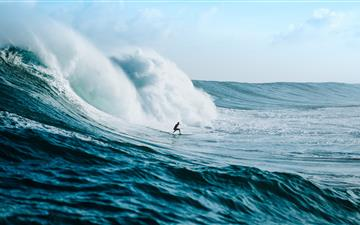 man surfing towards sea waves iMac wallpaper