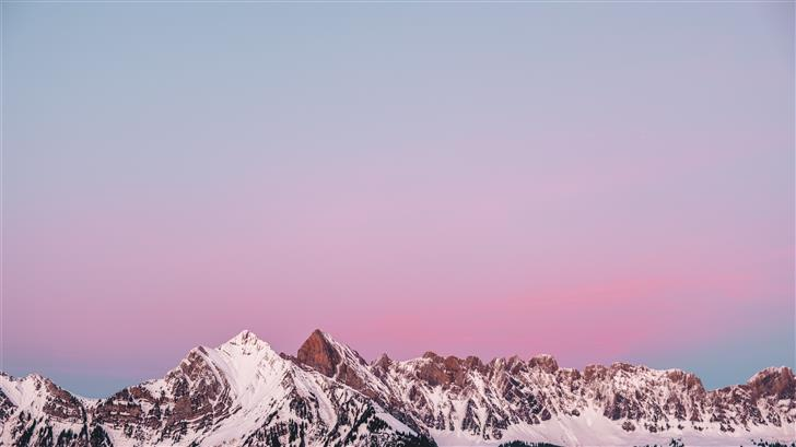 Lovely sunset behind a snowy mountain in Flums Swi Mac Wallpaper