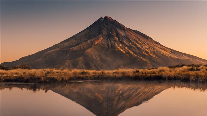 brown mountain near body of water during daytime Mac Wallpaper