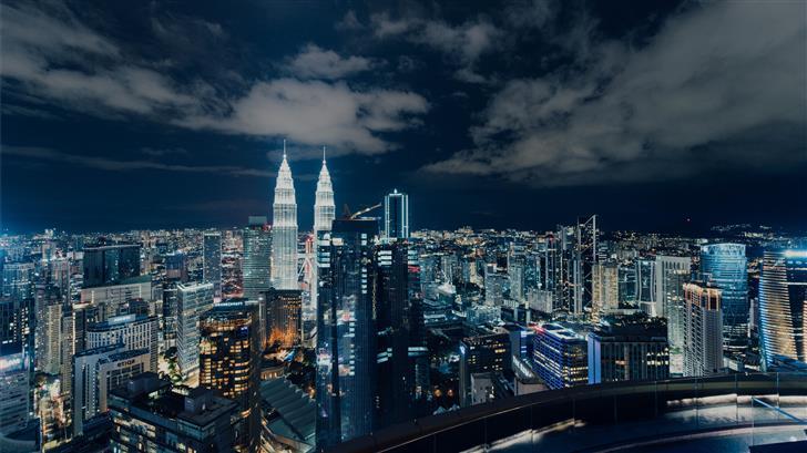 city skyline under gray cloudy sky during night ti Mac Wallpaper