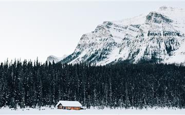snow covered cabin near forest MacBook Air wallpaper
