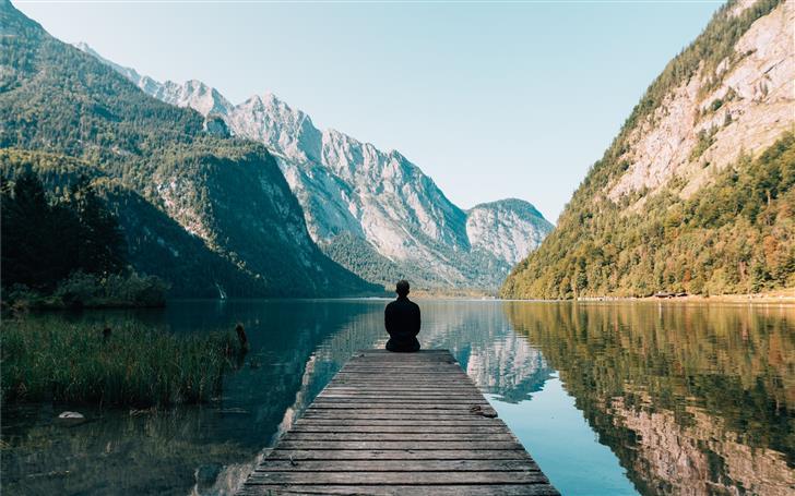 man sitting on gray dock Mac Wallpaper