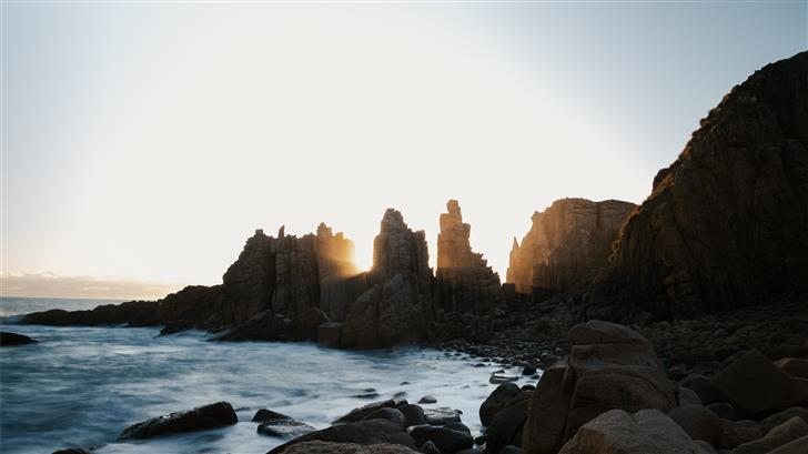stone formations on ocean during daytime Mac Wallpaper