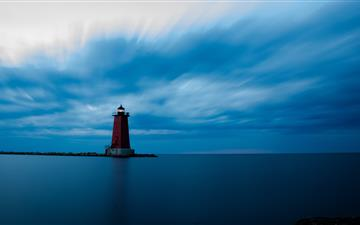 red and white lighthouse on top of hill iMac wallpaper