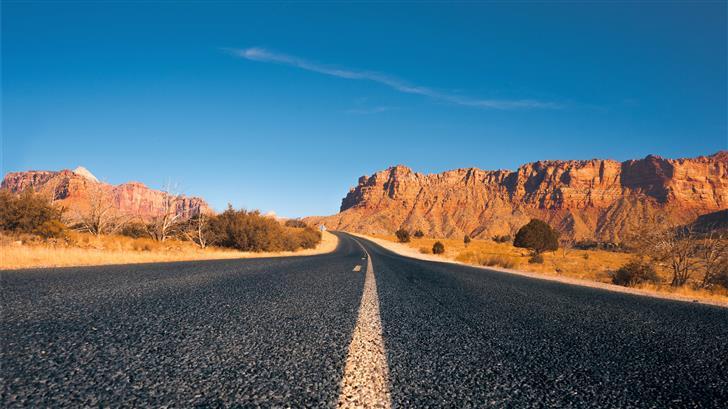 black asphalt road between brown rock formation un Mac Wallpaper