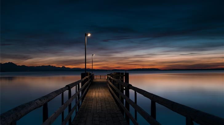 lamp post turned on at brown wooden dock Mac Wallpaper