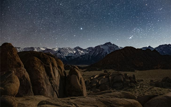 brown rocky mountain under blue sky during night t Mac Wallpaper