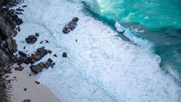 brown rocks on white sand beach 5k Mac Wallpaper