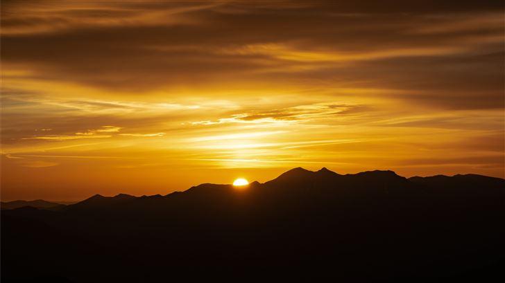 sun setting behind mountains Mac Wallpaper