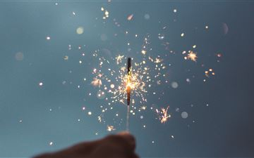 person holding lighted sparklers MacBook Pro wallpaper