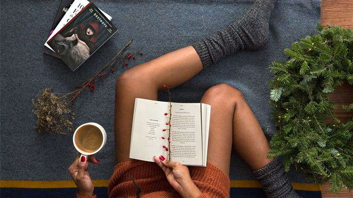 opened book on person's lap with gray socks Mac Wallpaper