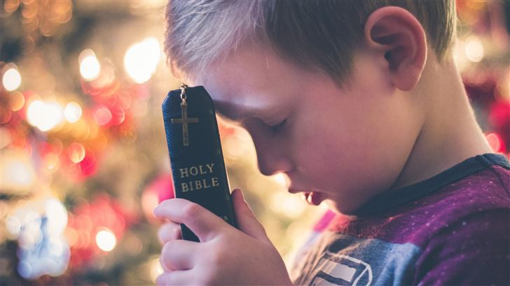 boy holding Holy Bible Mac Wallpaper
