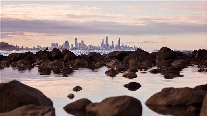 seashore rocks near city view of buildings 5k Mac Wallpaper