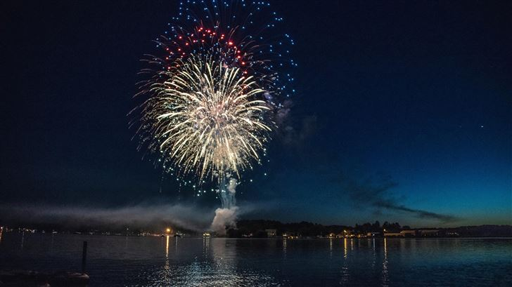 fireworks explosion above water body 8k Mac Wallpaper